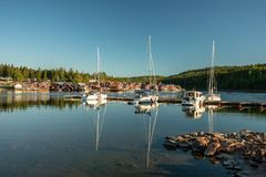 Summer view of a fishing camp by the Swedish east coast. Beautiful summer view of a fishing camp on the Swedish north east coast. With small red buildings in a stock image
