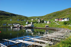 Summer view of fishing village Akkarfjord. Fishing village is located on the side of blue fjord. Soroya is photographed in summer. There are wooden houses on the Royalty Free Stock Images