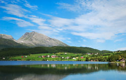 Summer view of the fjord with green shore. The blue sky and mountains are reflecting in smooth surface of the fjord. In the background a village is on the green Royalty Free Stock Images