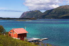 Summer view of Lofoten Islands with red rorbu. Beautiful summer daylight view of Lofoten Islands, Norway, with mountains, fjord, and small red rorbu used as Stock Photography