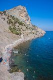Summer view seacoast. Sudak beach. Black Sea, Ukraine. SUDAK, UKRAINE - JULY 5: People swim and sunbathe at the city beach of Sudak on July 5, 2012 in Sudak stock photos