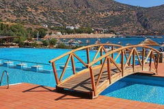 Swimming pool, foot bridge and beach in resort(Greece). Summer view with swimming pool,wood foot bridge and beach in mediterranean resort(Greece Stock Photos