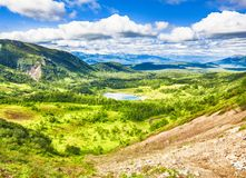 Summer view of valley with mountiщты, under blue sky with clouds. royalty free stock images