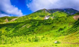 Summer view of volcano on Kamchatka, under blue sky with clouds royalty free stock photos