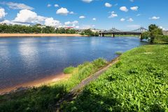 Summer view of the water surface and shores of the Volga river and the old Volga bridge in the background, city of Tver, Russia. Summer landscape evokes stock images