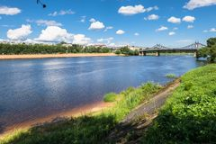 Summer view of the water surface and shores of the Volga river and the old Volga bridge in the background, city of Tver, Russia. Summer landscape evokes stock photo