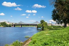 Summer view of the water surface and shores of the Volga river and the old Volga bridge in the background, city of Tver, Russia. Summer landscape evokes Royalty Free Stock Image
