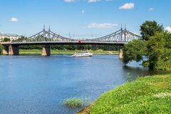 Summer view of the water surface and shores of the Volga river and the old Volga bridge in the background, city of Tver, Russia. Summer landscape evokes stock photos