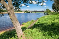 Summer view of the water surface and shores of the Volga river and the old Volga bridge in the background, city of Tver, Russia. Summer landscape evokes stock photography