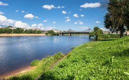 Summer view of the water surface and shores of the Volga river and the old Volga bridge in the background, city of Tver, Russia. Summer landscape evokes royalty free stock photos