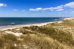 Summer view from west coast of Denmark. With ocean, blue sky, green grass and windmill in background stock photography
