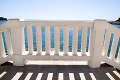 Summer view with white balustrade and empty terrace overlooking. White stairs that lead to the perfect blue sea and beach. Summer view with classic white stock photo