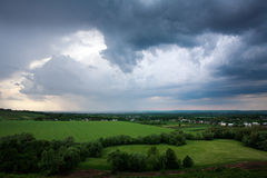 Summer village in green fields on background of storm clouds sky Royalty Free Stock Photography