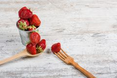Summer vitamin food. A bucket of fresh ripe fragrant strawberries and a wooden spoon and fork. Lie on a textured light wooden background. Food causing stock photo