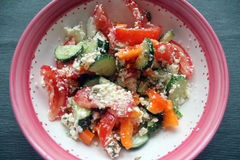 Summer vitamine salad. A salad with red tomatoes, green cucumbers, orange sweet pepper and cottage cheese in a deep bowl with pink frame Royalty Free Stock Photography