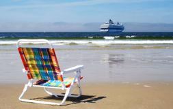 Summer is waiting. Empty chair on a beach with ocean and cruise ship in the background stock image