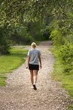 Summer Walk. Girl walking on path royalty free stock photography