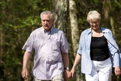 Summer walk. Senior couple out on a summer day strolling through the wood Royalty Free Stock Images
