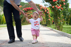 Summer walk. Childs first steps in the fathers strong hands Stock Photo