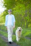 Summer walk. Portrait of cute lad and his fluffy friend walking outdoors Royalty Free Stock Images