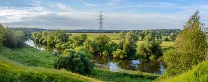 Summer warm evening. Panorama with river views from the footbridge. The village is in the background. Reflection of blue sky in the river water Royalty Free Stock Images