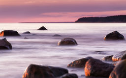 Summer warm seascape with stones and focus at one stone. Baltic Sea, Latvia, evening and long exposure Royalty Free Stock Photo