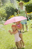 Summer water fun. Smiling woman spaying little girls with water from a garden hose in the summertime Stock Photography