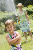 Summer water fun with garden hose rain. Pretty woman spraying little girl with water from a garden hose in the Summertime Stock Image