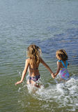 Summer water joy. Sisters run together into the sea Stock Image