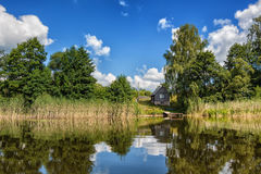 Summer water landscape with a moorage and a house Royalty Free Stock Photos