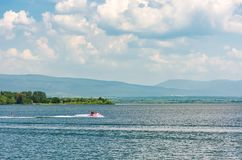 Summer water sports on Zemplinska Sirava lake. Slovakia. Lovely place for vacation or weekend in summer. people have fun while water skiing and riding water Royalty Free Stock Image