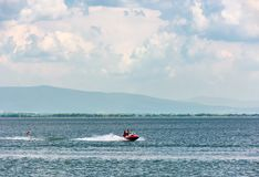 Summer water sports on Zemplinska Sirava lake. Slovakia. Lovely place for vacation or weekend in summer. people have fun while water skiing and riding water Stock Images
