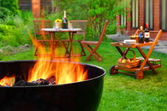 Summer Weekend BBQ Scene With Grill On The  Backyard Garden. Summer Weekend BBQ Scene On The Backyard. Flaming Charcoal Grill Close Up. Outdoor Wooden Furniture Royalty Free Stock Image