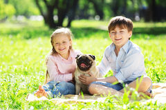 Summer weekend in park. Adorable boy and girl in summer park with their dog Royalty Free Stock Images