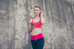 Summer, wellbeing, wellness, music and work out! Low angle portr. Ait of sporty young lady in fashionable sport wear is listening to music and smiling, will Stock Images