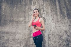 Summer, wellbeing, wellness, music and work out! Sporty young la. Dy in fashionable sport wear is listening to music and smiling, will start her training now Stock Images