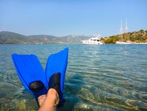 Summer wellness holidays by the sea concept, feet in fins on the beach of Love bay Poros island, Agrosaronikos, Greece. Royalty Free Stock Images