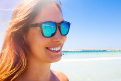 Summer white smile and fun. Sunglasses woman. Sea travel. Young and beautiful smiling woman with sunglasses. Blue sea in the background. Beach holiday. Concept Stock Image