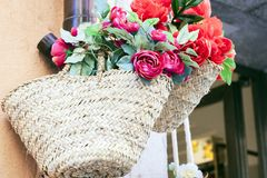 Summer wicker bags made of straw and rattan with textile flowers on the market in Taormina, Sicily, Italy stock photos