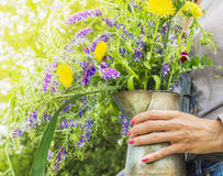 Summer wild flowers bunch in old jug in hand Stock Photo