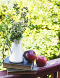 Summer wild flowers in glass vase, old books and apples. Royalty Free Stock Images