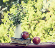 Summer wild flowers in glass vase, old books and apples. Royalty Free Stock Image