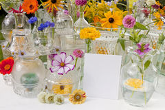 Summer Wild Flowers. A large display of summer wild flowers and glassware on a white table outside Royalty Free Stock Image