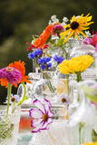 Summer Wild Flowers. A large display of summer wild flowers and glassware on a white table outside Stock Image