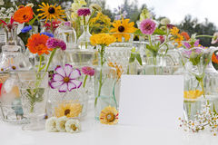 Summer Wild Flowers. A large display of summer wild flowers and glassware on a white table outside Royalty Free Stock Photos