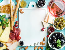 Summer wine snack set. Glass of rose, meat, cheese, olives, honey, bread sticks, nuts, capers and berries with white Royalty Free Stock Photo