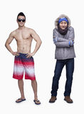 Summer and winter, young man in shorts and young man in winter coat,  opposite, studio shot Stock Image