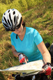 Summer. Woman on bicycle reading a map. Royalty Free Stock Images