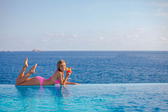Summer woman drinking cocktail in Mallorca. In infinity pool Royalty Free Stock Image