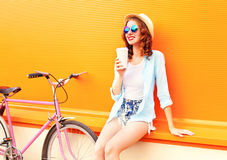 Summer woman drinks coffee of cup near retro vintage pink bicycle. On a colorful orange background royalty free stock photo